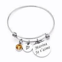 Bracelet jonc avec son médaillon rond argenté gravé avec un texte.